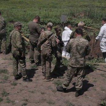 У захороненні на Донбасі знайшли тіла з російськими шевронами (фото)